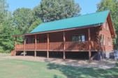 2502 New Hope Road, Big Sandy, TN 38221 - Image 1: This beautiful log home was completed in 2016 and features a full length front porch