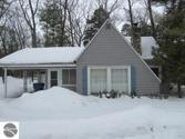 4398 Lake Avenue, Interlochen, MI 49643 - Image 1: This cottage is located along Lake Ave.  Has a carport outside the cottage.
