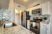 7151 Gaston Avenue Unit 616, Dallas, TX 75214 - Image 1: Stainless steel appliances, white cabinets, apron sink, arabesque glass and tile backsplash, water filtration system at the sink.