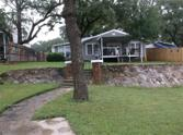 477 Williamson Road, Bowie, TX 76230 - Image 1: Lake side of house with rock retaining wall