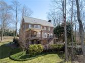 312 Lake Point Lane, Belews Creek, NC 27009 - Image 1: This is the lake side of the home featuring a main level deck that has a covered dining/grilling area.  Lower level deck is completely dried in due to the sealed upper deck.  Fantastic Landscaping!